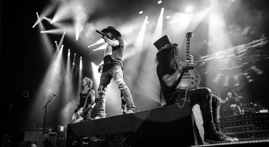 Black and white image of Axl, Slash and Duff performing on stage